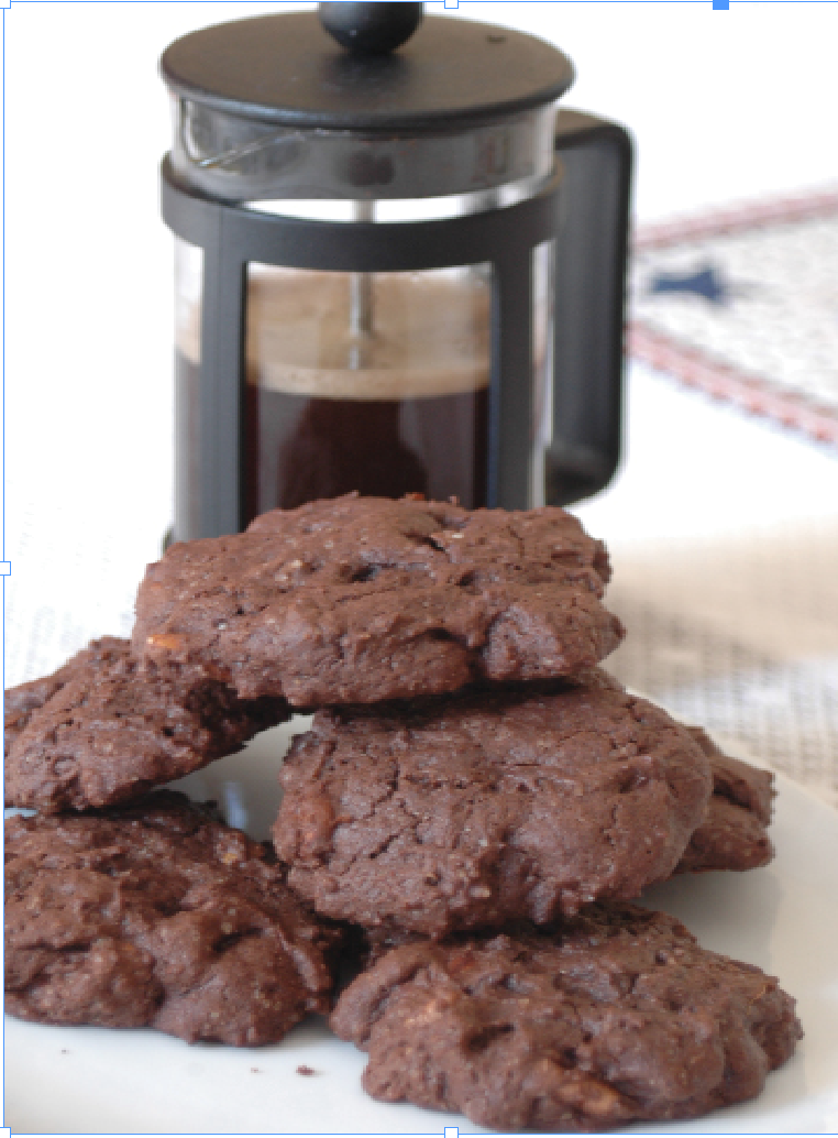Chocolate Cookies stacked in front of a French press with coffee