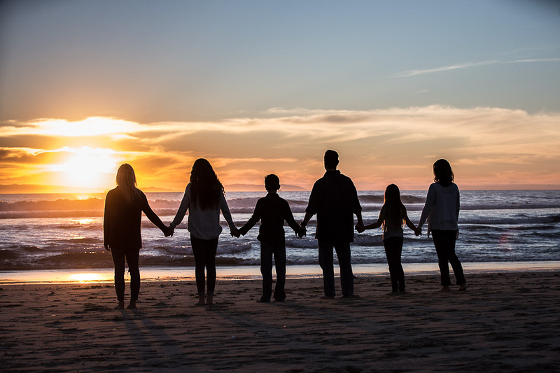 Family standing on beach looking out over the sunset