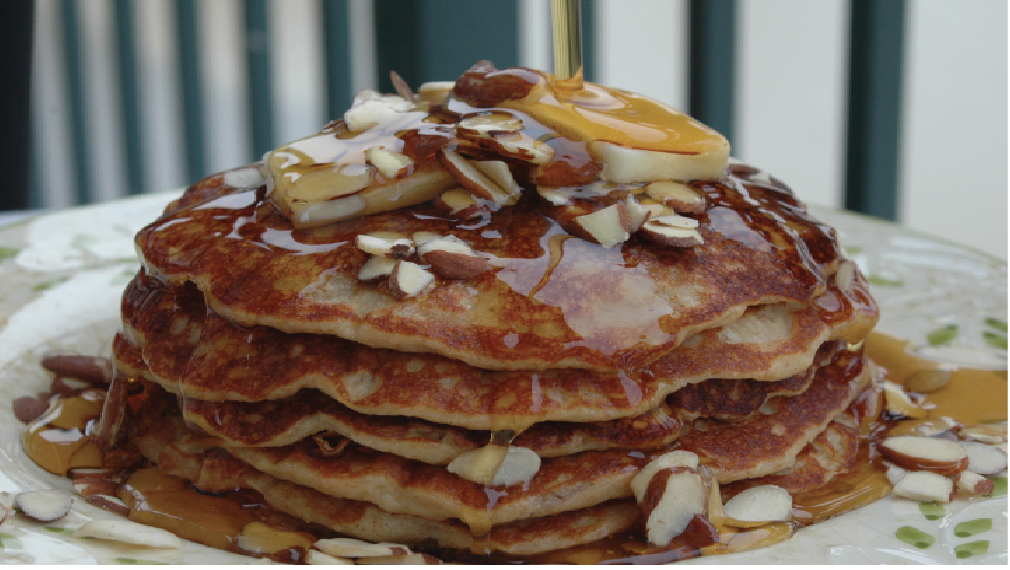 Pancakes sit on a place and syrup drips down ver the top of them covered in sliced almonds